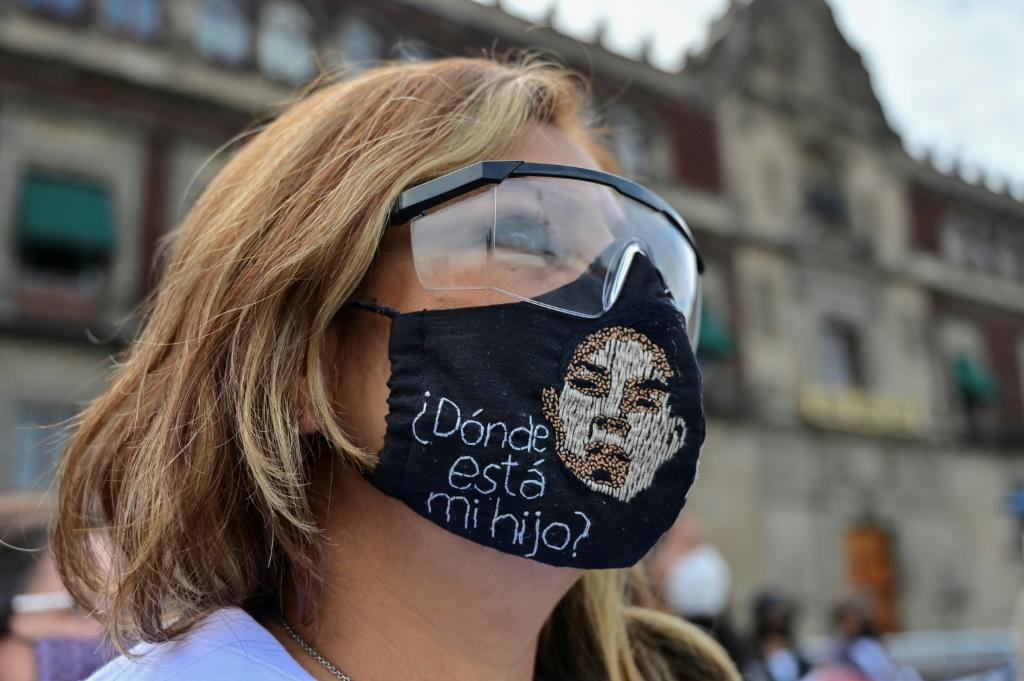 A woman wears a face mask reading 'Where is my son?' at a protest in Mexico City