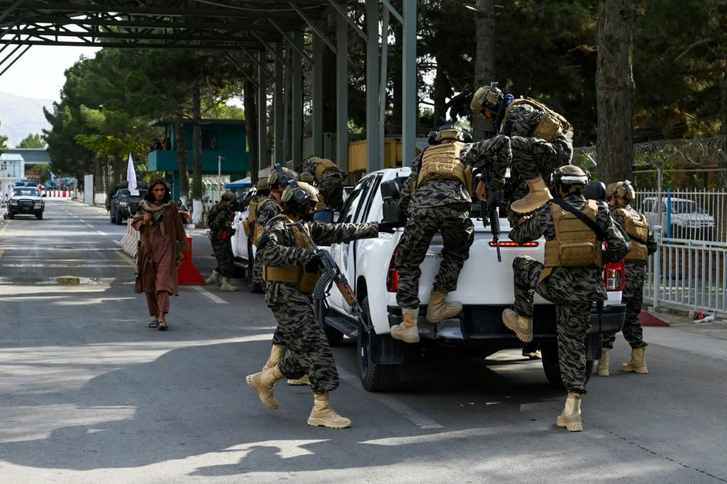 Taliban 'Badri 313' special force fighters arrive at the main entrance gate of Kabul airport after the last US troops left
