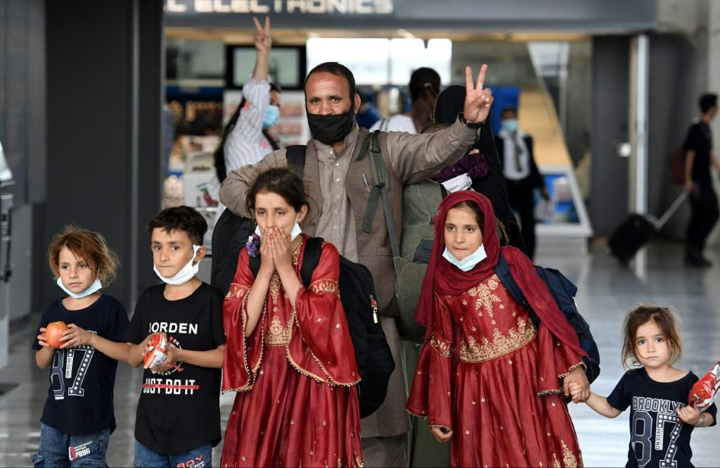 Afghan refugees arrive at Dulles International Airport on August 27, 2021 after being evacuated