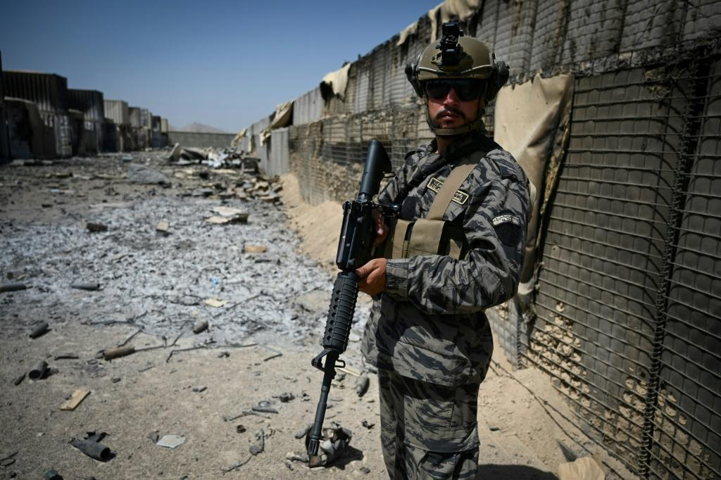 A Taliban Badri 313 unit officer stands guard at the destroyed CIA base in Deh Sabz District