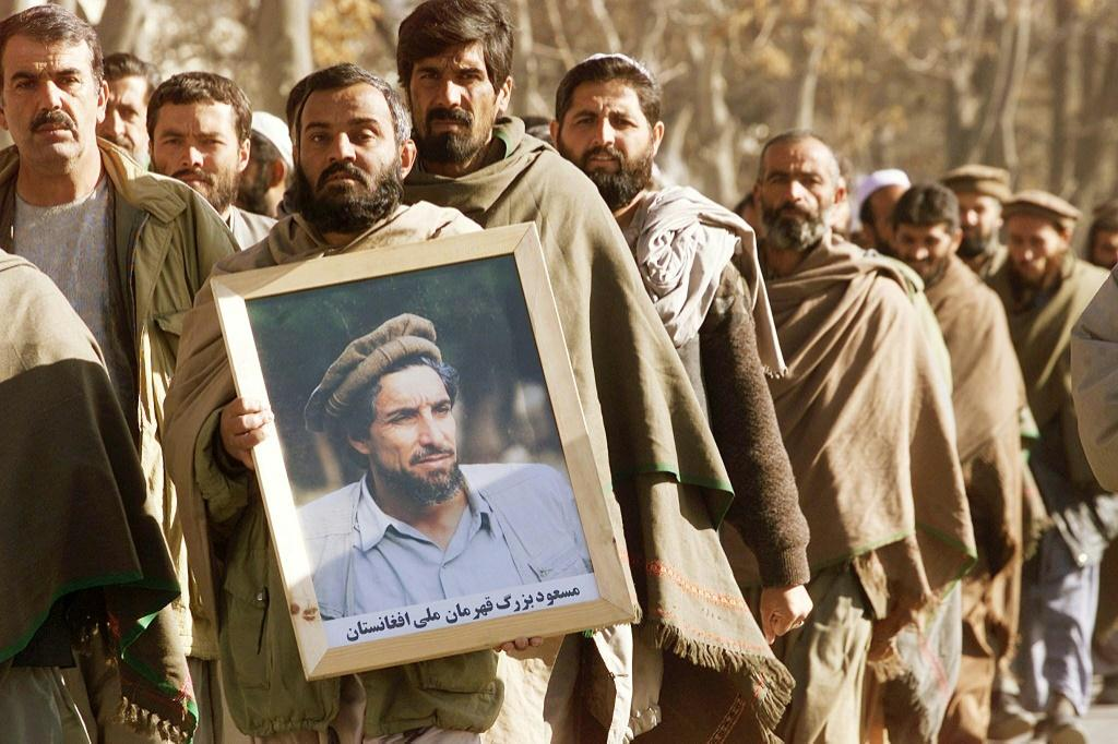 An Afghan man holds a portrait of Ahmad Shah Massoud in December 2001