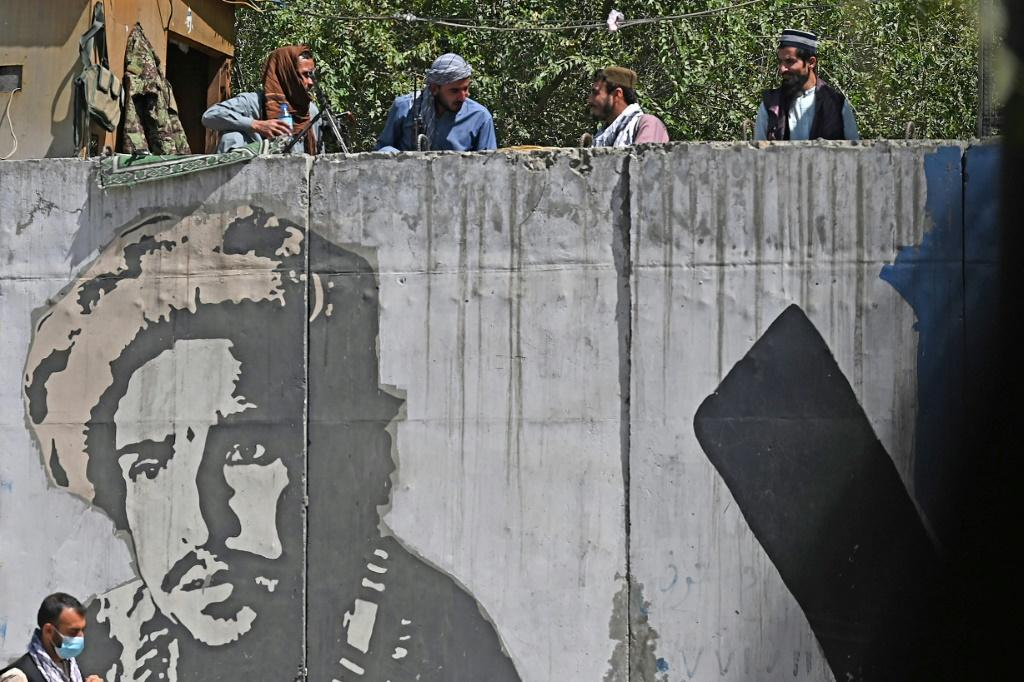 Taliban fighters by a concrete wall painted with an image of Ahmad Shah Massoud
