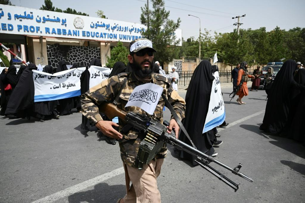An armed Taliban fighter escorted the women as they rallied in favour of the new Islamist regime