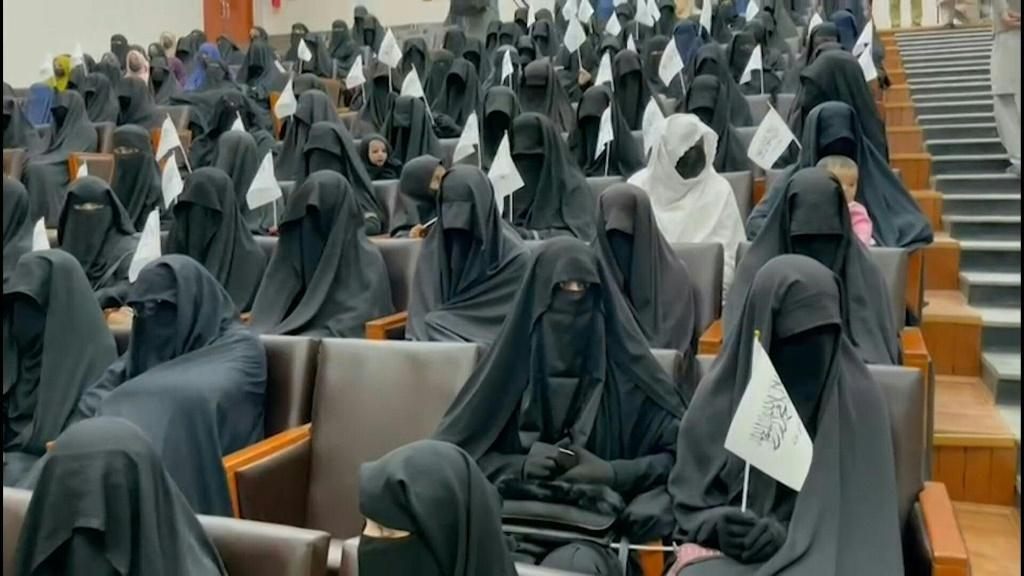 SOUNDBITE About 300 Afghan women, fully covered in attire deemed acceptable to the Taliban and holding their white-and-black flags, gather at a Kabul university in a show of support for the Islamists. The display comes as the Taliban move to snuff out civ