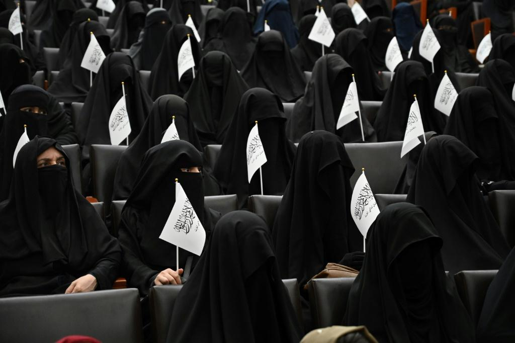 Veiled women -- covered head-to-toe in accordance with strict new dress policies for education -- waved Taliban flags as speakers railed against the West and expressed support for the Islamists' policies in Kabul