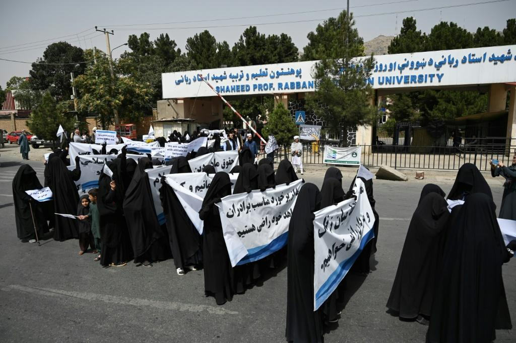 Veiled women held banners and placards while marching during a pro-Taliban rally outside the Shaheed Rabbani Education University in Kabul on September 11, 2021. Afghan women wearing full face veils sat in rows at a Kabul university lecture theatre Saturd
