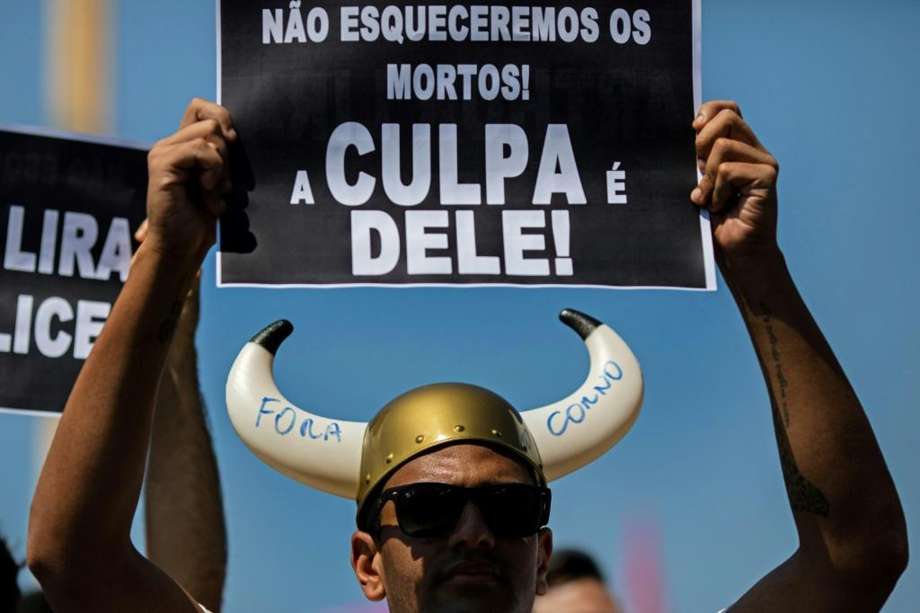 """A man holds a sign reading """"We won't forget the dead! It is his fault!"""" -- in allusion to President Jair Bolsonaro -- during a demonstration demanding his impeachment"""