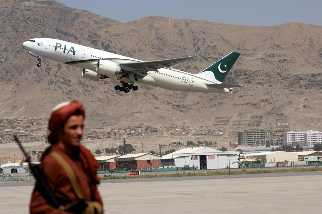 A Taliban fighter stands guard as a Pakistan International Airlines plane takes off from Kabul
