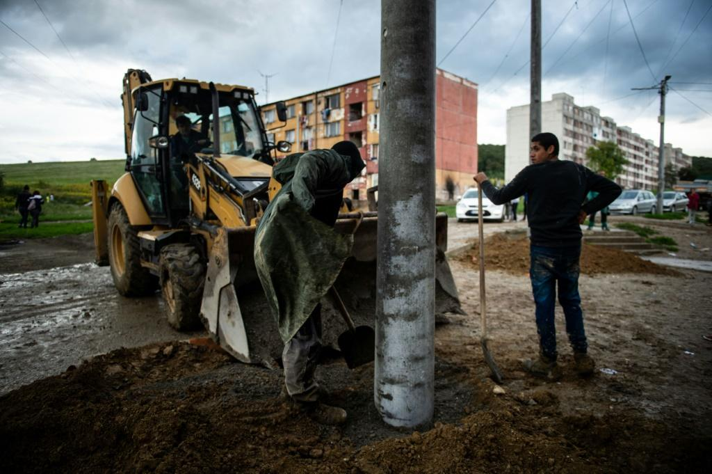 Workers install new street lights in the Lunik IX district ahead of the papal visit