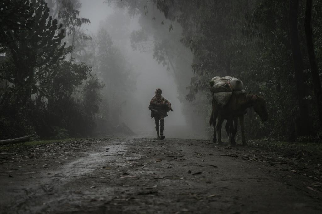 A boy walks in the fog near Chenna, which people have fled since the mass killings