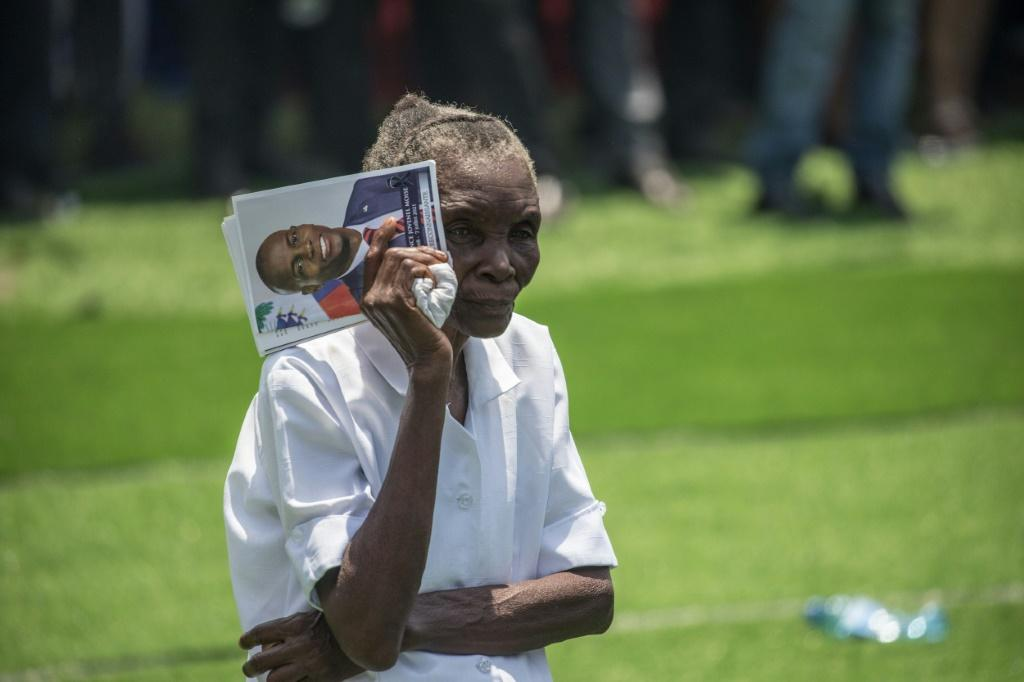 A woman holds a picture of slain Haitian President Jovenel Moise during his funeral on July 23, 2021, in Cap-Haitien, Haiti