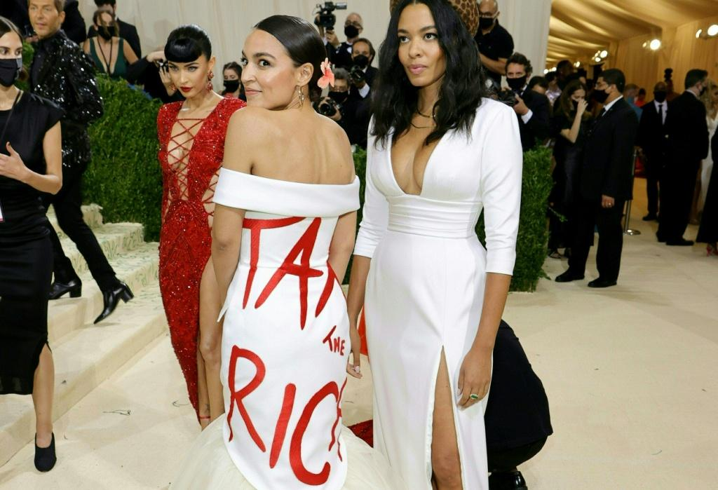 """Democratic House Representative Alexandria Ocasio-Cortez (L) raised eyebrows when she wore a dress declaring """"Tax the Rich"""" at the Met Gala in New York on September 13, 2021"""