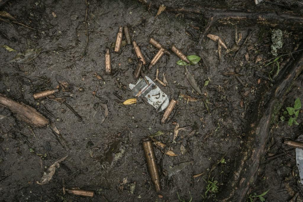 Spent bullet casings litter the ground near a mass grave in Chenna