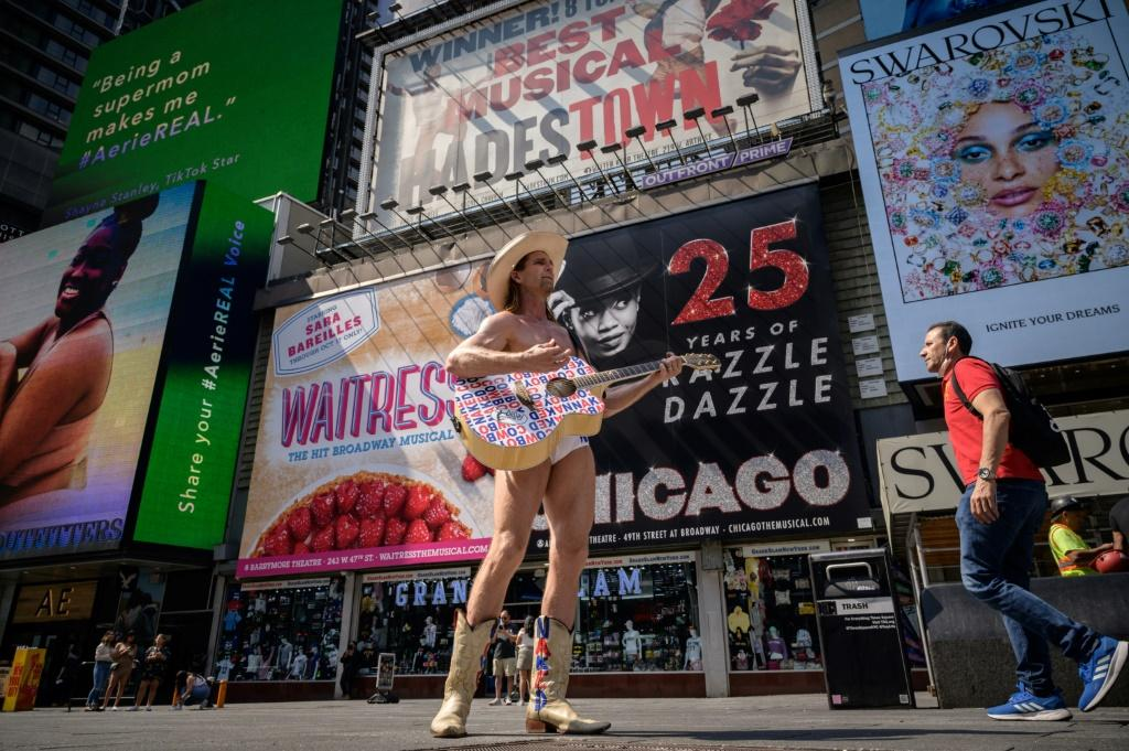 The Naked Cowboy stands before billboards advertising broadway musicals, on Times Square in New York on September 14, 2021