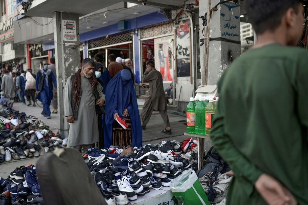 A burqa-clad woman checks footwear displayed on a stall at a market area in Kabul