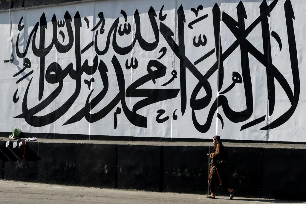 A man walks past a wall mural depicting the Taliban flag in Kabul
