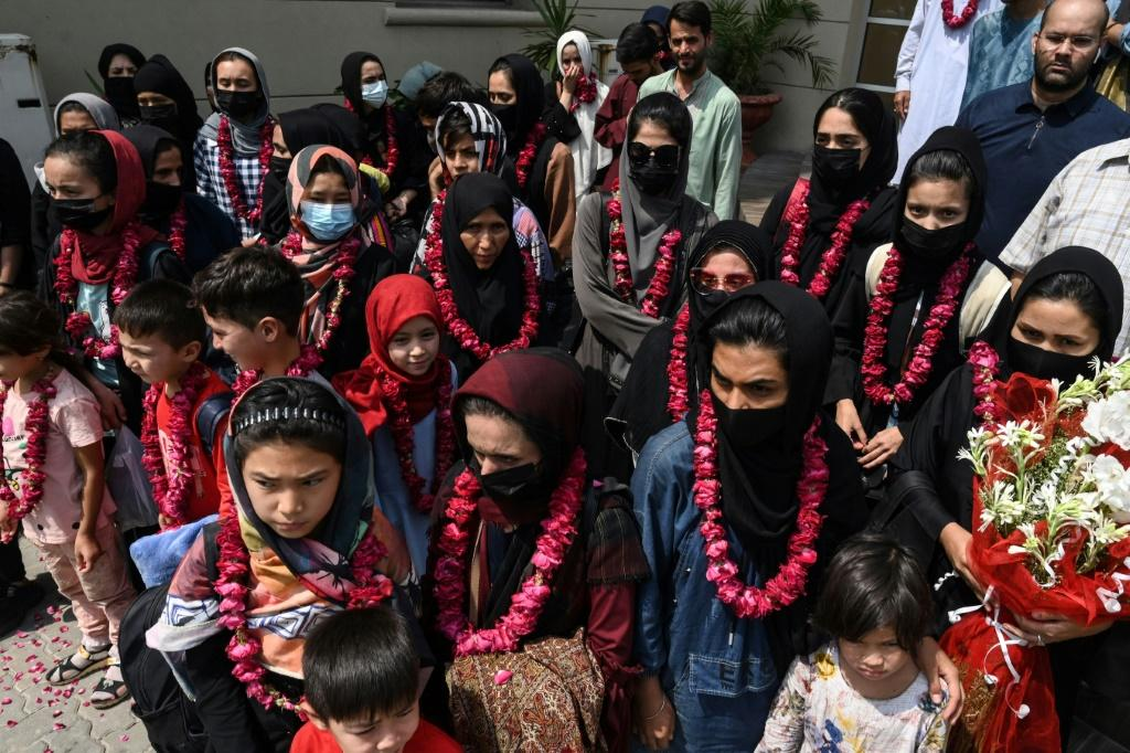 The team wore garlands and dressed in burqas as they arrived at the Pakistan Football Federation in Lahore