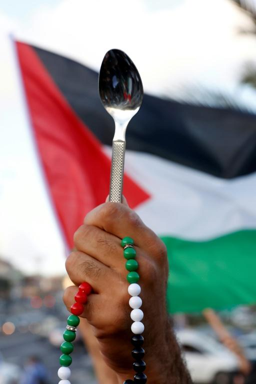 Arab Israeli protesters lift spoons during a demonstration in the mostly Arab city of Umm al-Fahm in northern Israel in September 2021