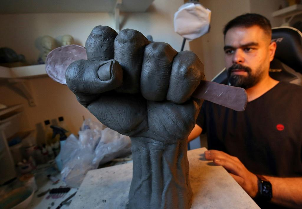 """Kuwaiti artist Maitham Abdal works on his sculpture, """"Spoon of Freedom"""", at his home workshop in Kuwait City"""