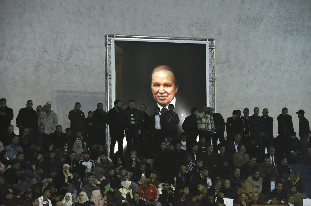 Supporters of Algeria's National Liberation Front (FLN) party gather on February 9, 2019 in the capital Algiers to call upon President Abdelaziz Bouteflika (shown in a poster) to run for a fifth term -- his decision to stand sparked mass protests