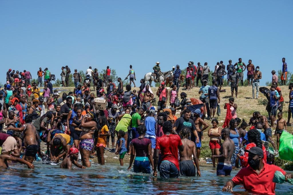 Haitian migrants, part of a group of over 10,000 people staying in an encampment on the US side of the border at Del Rio, Texas, cross the Rio Grande river to get food and water in Mexico.