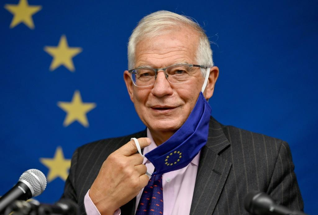Top EU diplomat Josep Borrell removes his face mask prior to speaking during a press conference following a meeting at the United Nations of EU foreign ministers that touched on a US-French row
