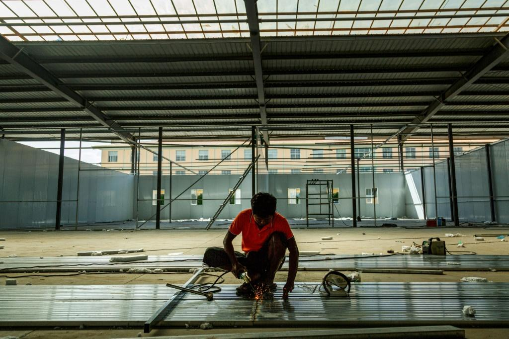 A labourer works to construct a new Covid-19 coronavirus quarantine centre in 115 Mile in Muse, near the China-Myanmar border