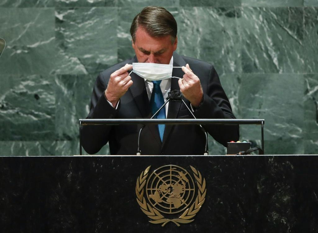 Brazil's President Jair Bolsonaro puts back on a protective facemask after he addresses the UN General Assembly