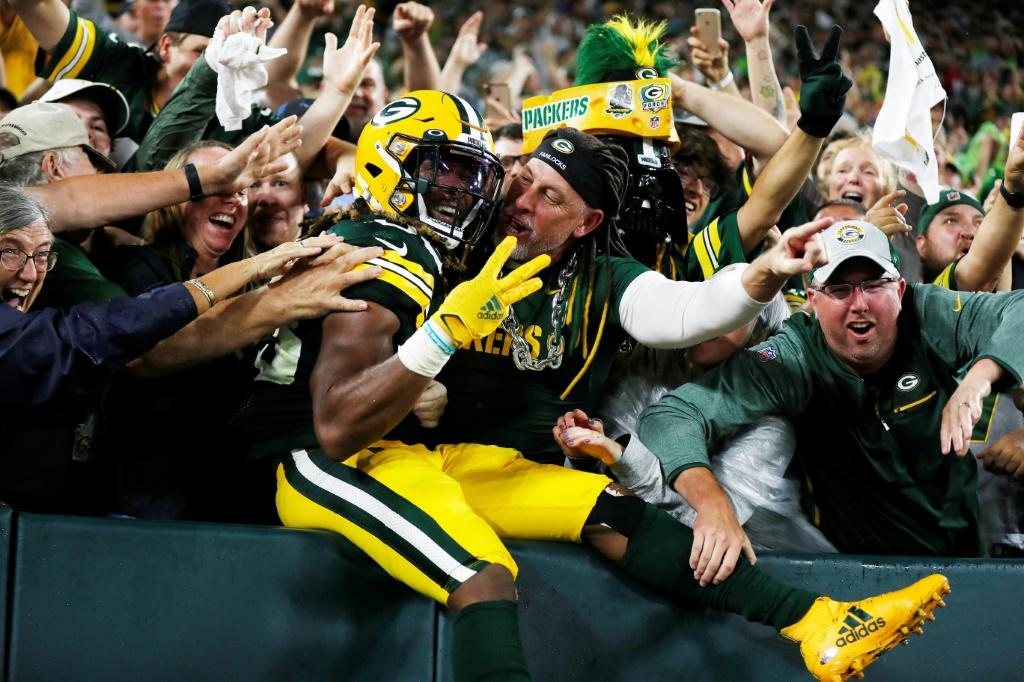 Jones celebrates his third touchdown of the night against the Detroit Lions with Green Bay fans during the second half at Lambeau Field