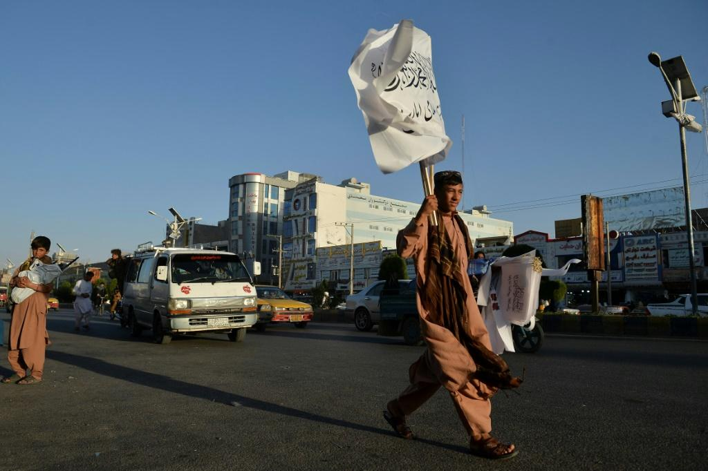 A boy selling Taliban flags looks for customers while walking along a road in Herat