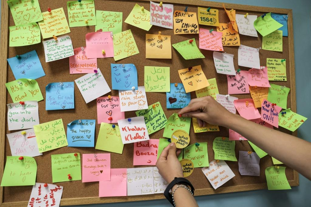 A woman places a note on a post-it board at the offices of Embrace, which says it receives around 1,100 calls a month