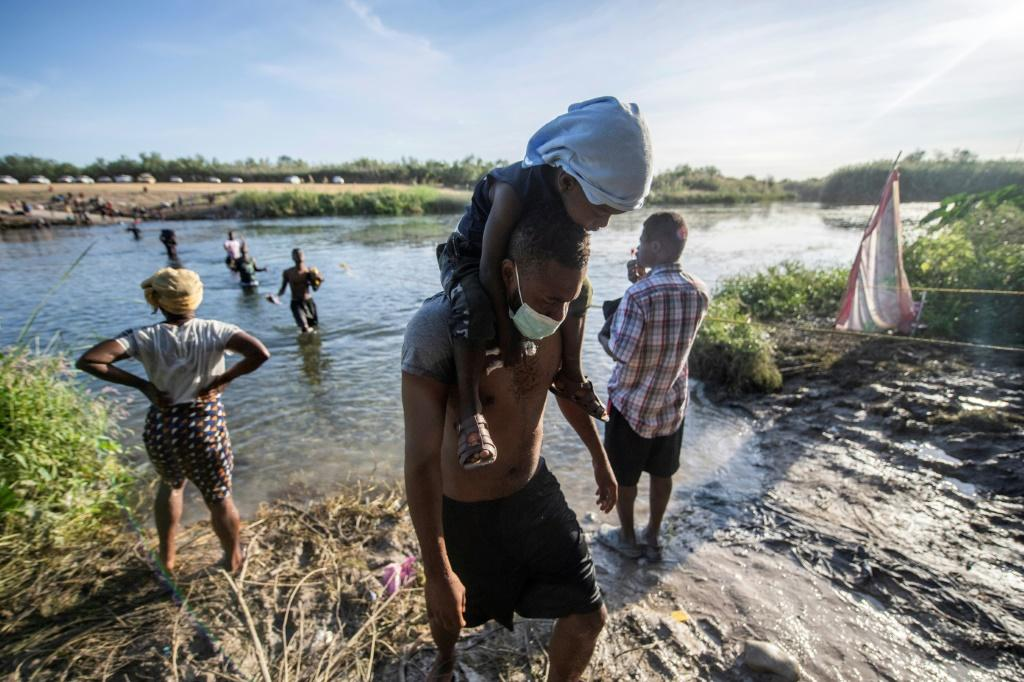 Haitian migrants hoping to enter the United States cross the Rio Grande river to get food and water in northern Mexico