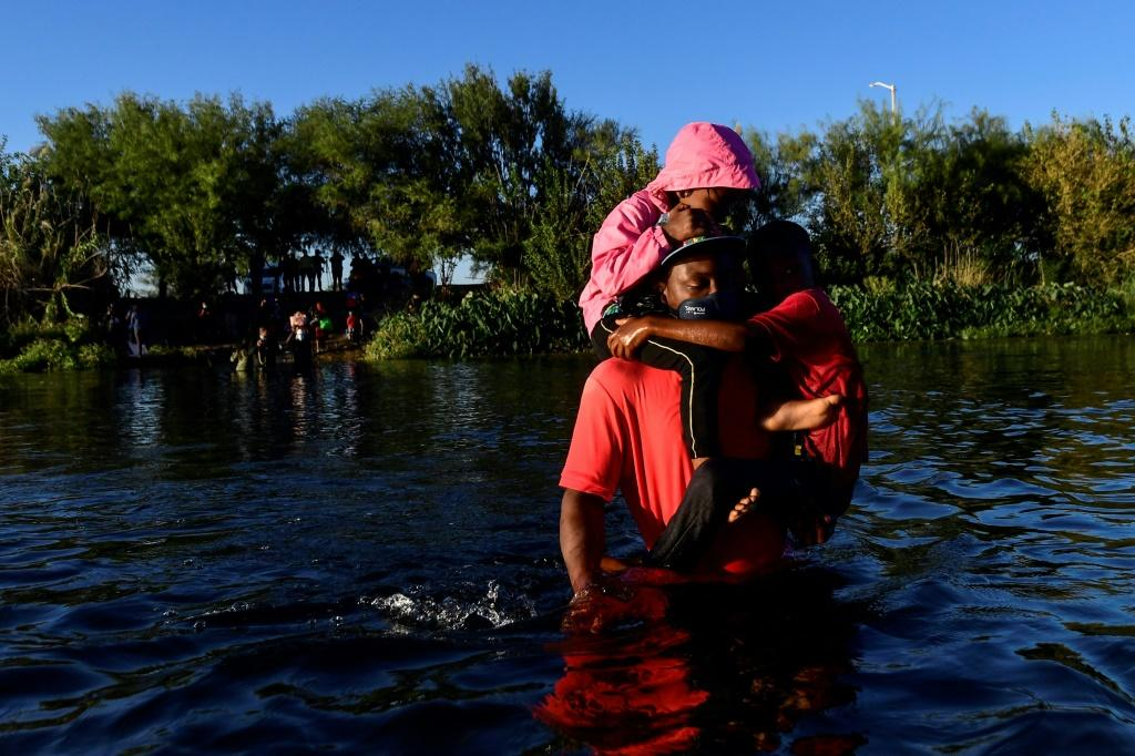 Haitian migrants cross the Rio Grande river that separates Mexico and the United States
