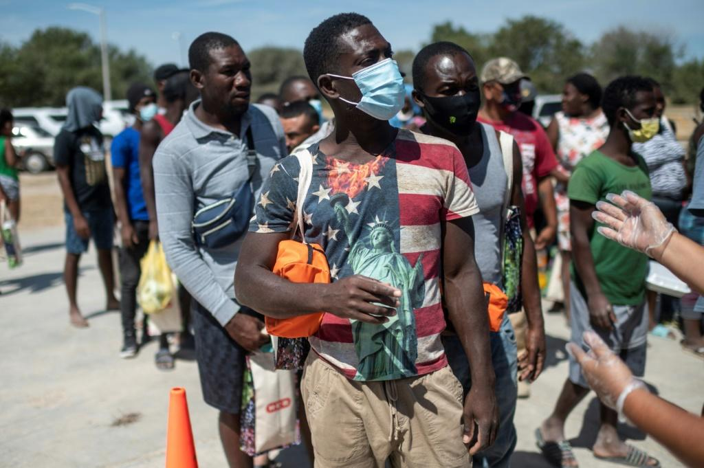 Haitian migrants queue to get food at a shelter in Ciudad Acuna, Mexico, across the border from Del Rio, Texas, where many have traveled hoping to remain in the United States.