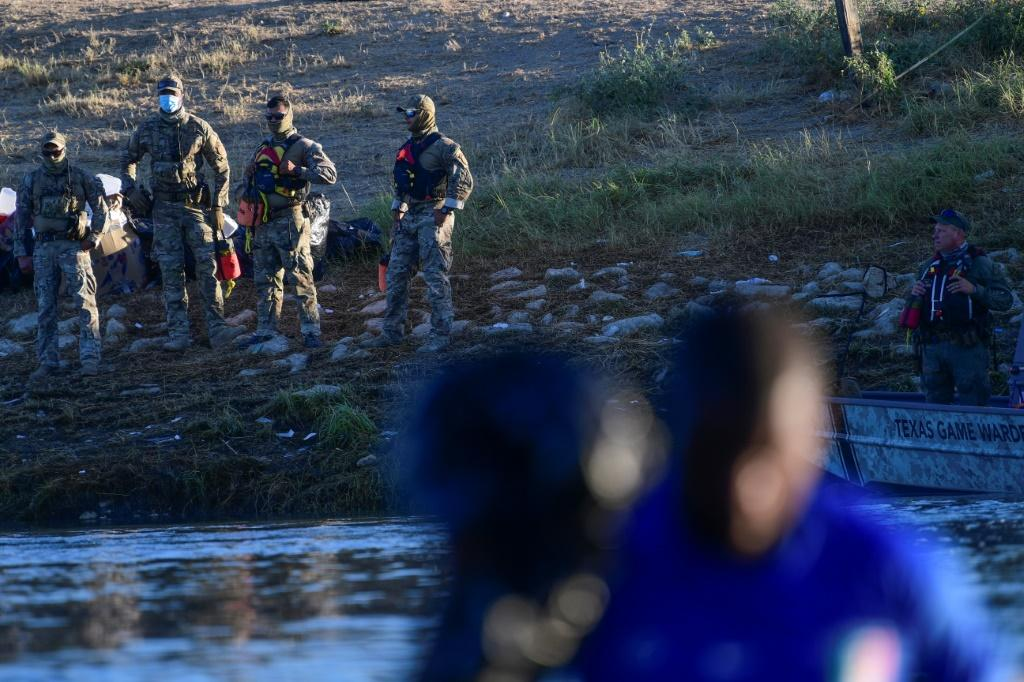 United States Border Patrol agents stand guard on the banks of the Rio Grande river at the border with Mexico