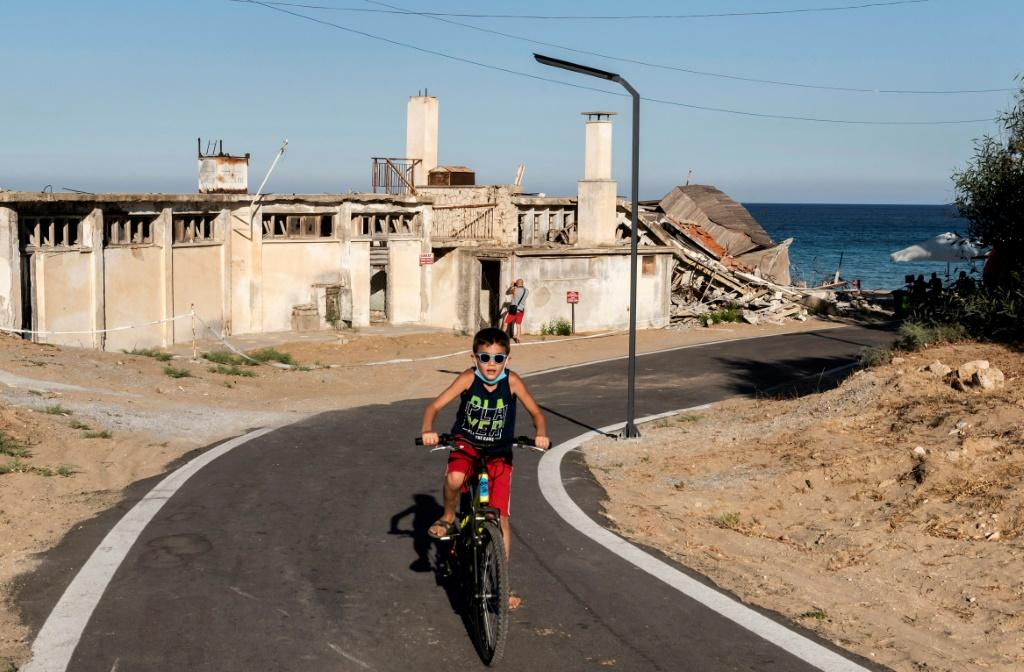 A child rides a bicycle on a street lined with derelict buildings in the fenced-off area of Varosha in northern Cyprus in June 2019 ahead of Turkish-backed plans to reopen the resort
