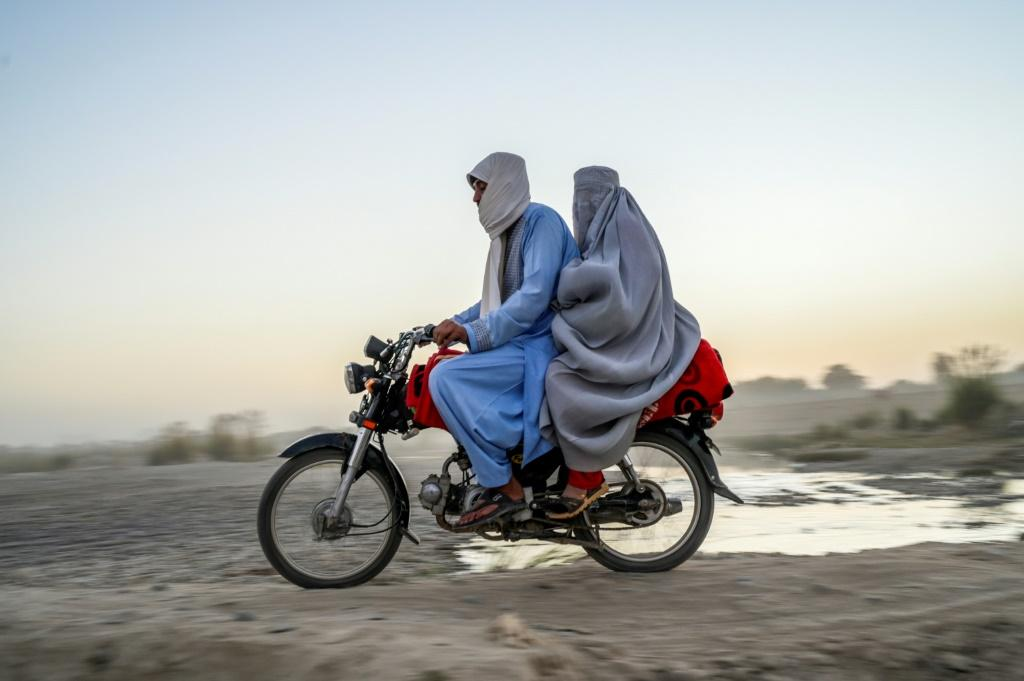 A woman wearing a burqa rides on the back of a mortorbike in Kandahar