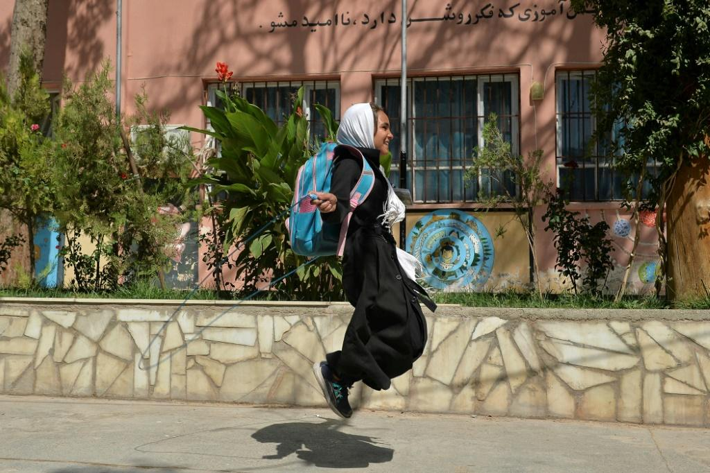 A young girl skips on a rope outside her primary school in Herat