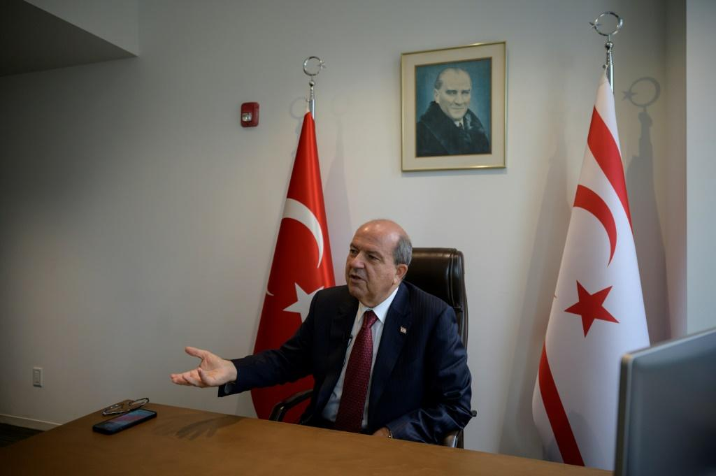 Turkish Cypriot leader Ersin Tatar sits beneath a portrait of the founder of modern Turkey, Kemal Ataturk, as he speaks with AFP in his office at the Turkish Center near the United Nations