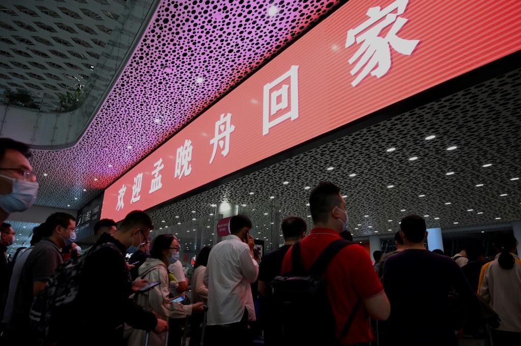 """A red banner hanging at Shenzhen airport arrivals hall read """"Welcome home Meng Wanzhou"""" and a crowd of about 200 supporters gathered waving Chinese flags and banners"""