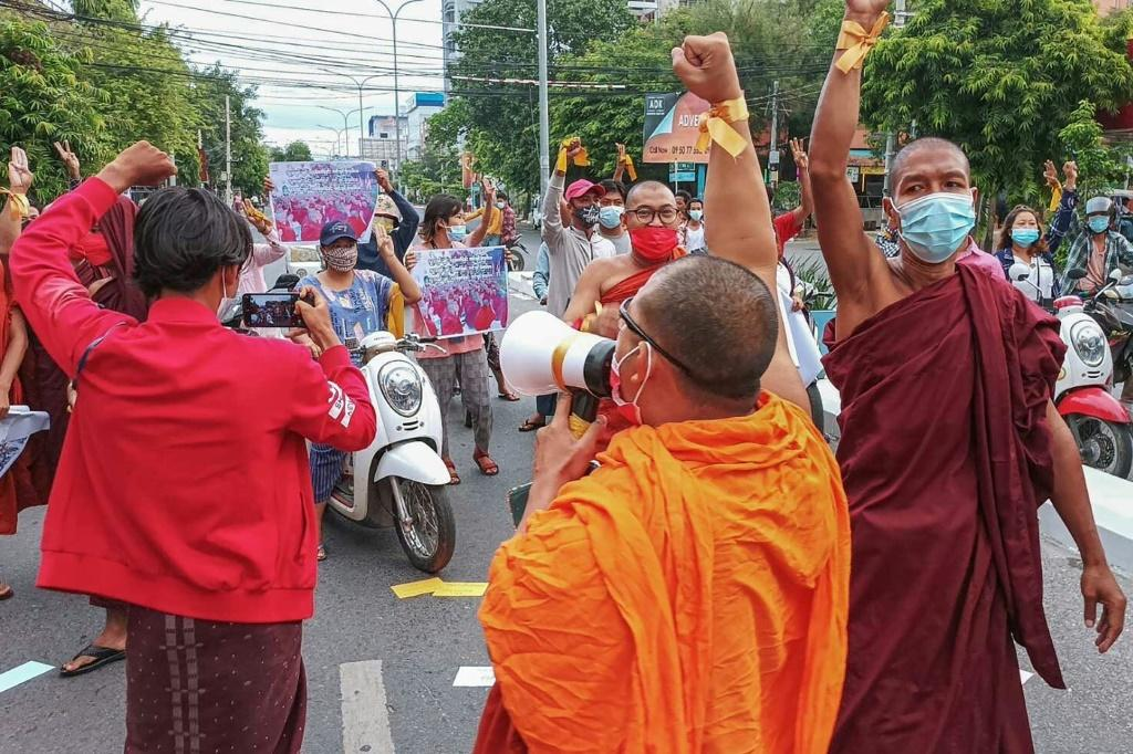 Dozens of monks in their bright orange and crimson robes marched through the streets of Mandalay