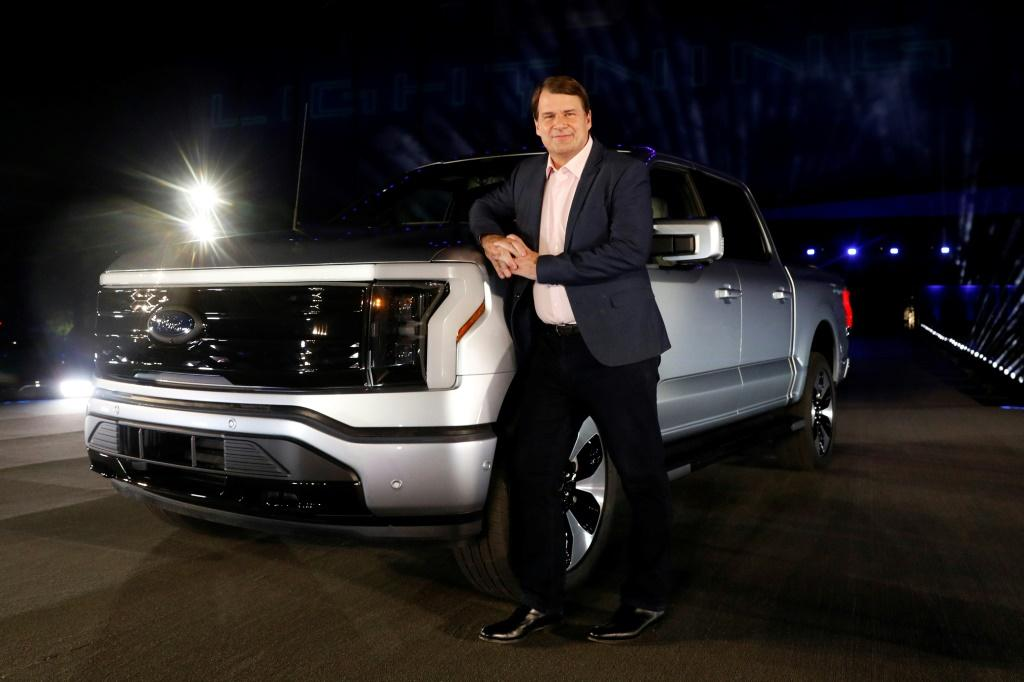 """Ford Motor Company's CEO Jim Farley poses next to the newly unveiled electric F-150 Lightning outside of their Dearborn, Michigan headquarters in May 2021; he said the company seeks to deliver electric vehicles """"for the many rather than the few"""