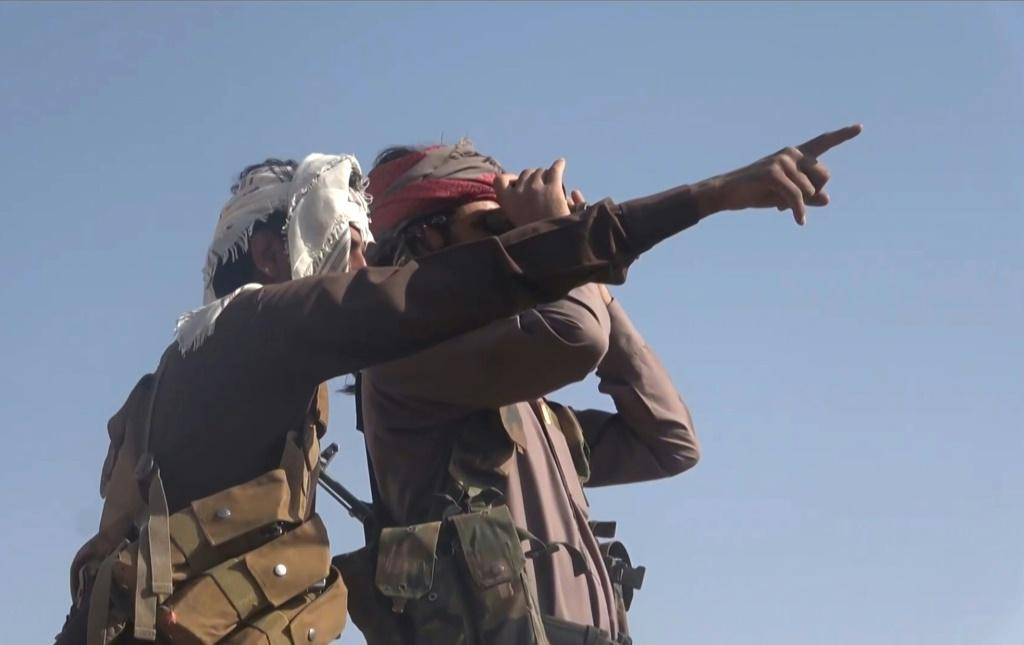 A grab from an AFPTV video shows Yemeni pro-government fighters looking at positions of the Iran-backed Huthi rebels near the loyalists' last northern bastion, the strategic city of Marib, on September 27