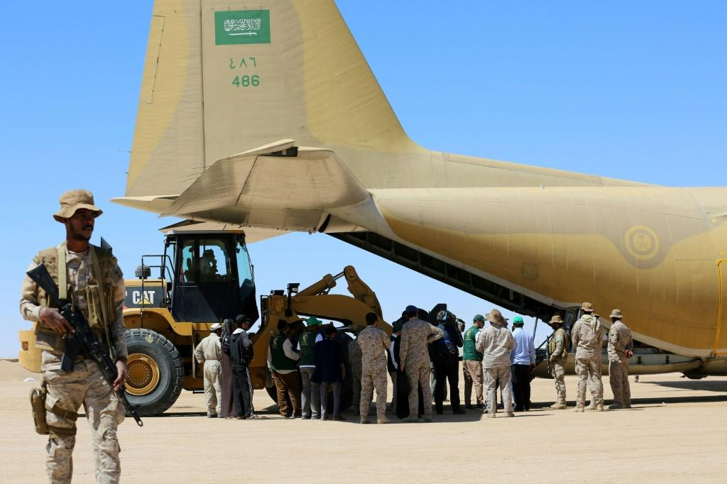A picture taken on February 8, 2018 shows Saudi soldiers standing guard as workers unload aid from a Saudi air force cargo plane at an airfield in Yemen's central province of Marib