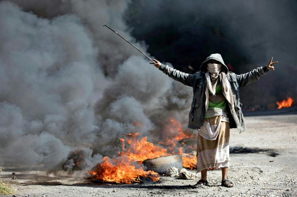 A Yemeni man next to burning tyres during protests calling for the removal of the Saudi-backed coalition government and deteriorating economic and living conditions, in Yemen's third city of Taez on September 27