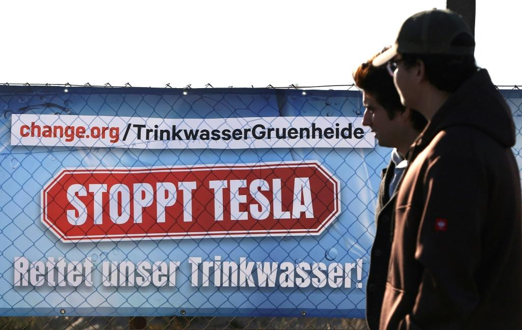 Signs protesting Tesla's new car factory were visible near the Tesla event
