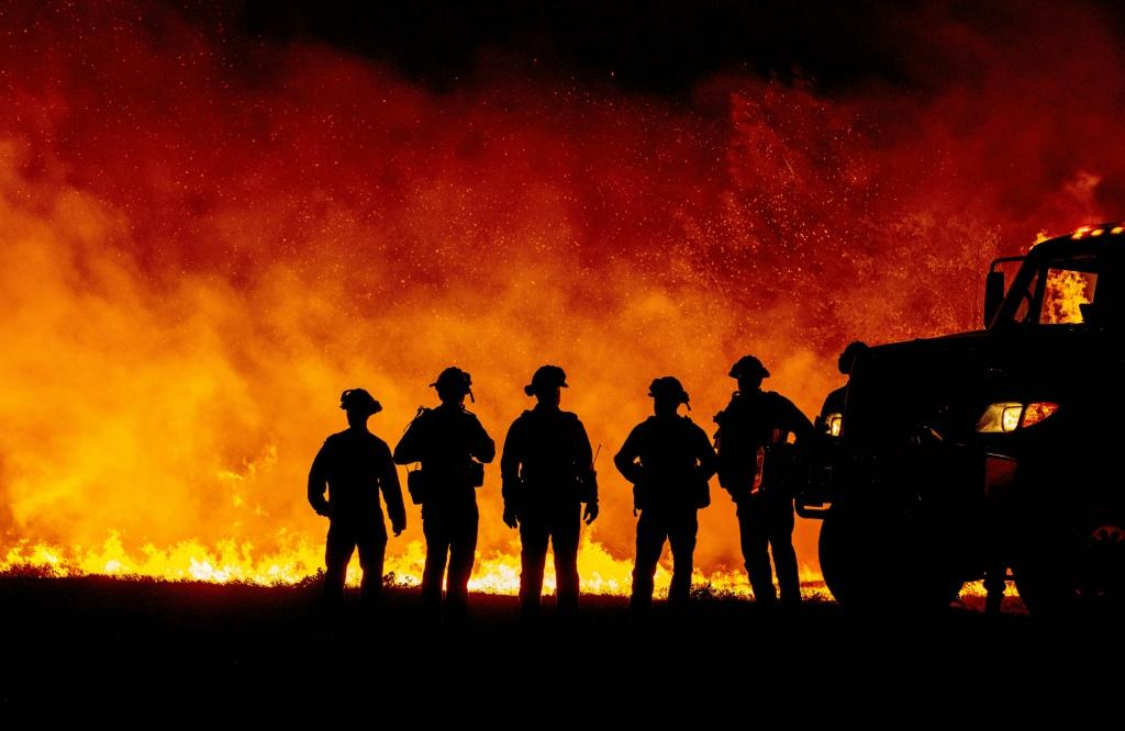 Fire fighters watch as flames quickly spread across a road at the Bear fire in Oroville, California in September 2020, one of a number of worsening disasters that experts have linked to climate change