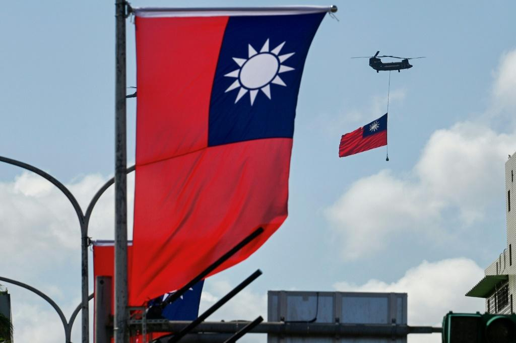 A CH-47 Chinook helicopter carries a Taiwan flag during national day celebrations in Taipei on October 10, 2021