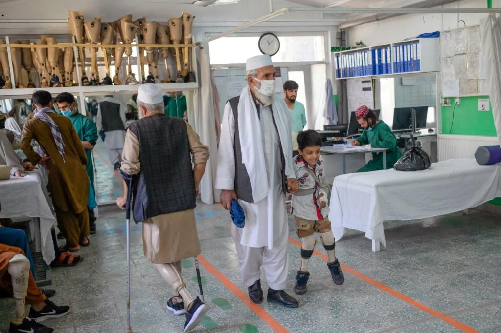 A child walks with his new prosthetic legs assisted by a relative at an International Committee of Red Cross Rehabilitation Centre in Kabul