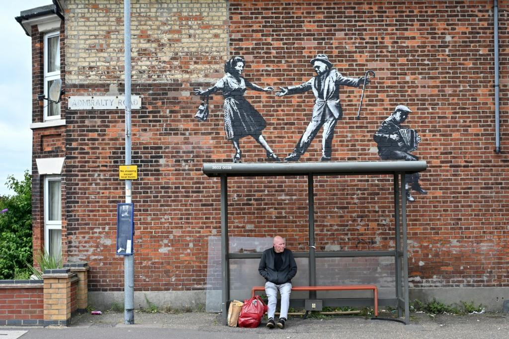 A graffiti artwork thought to be by Banksy shows a couple dancing to an accordion player above a bus stop